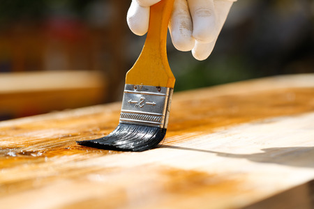 doityourself: Painter holding a paintbrush over wooden surface, protecting wood for exterior influences and weathering. Carpentry, wood treatment, hard at work, home improvement, do-it-yourself concept.