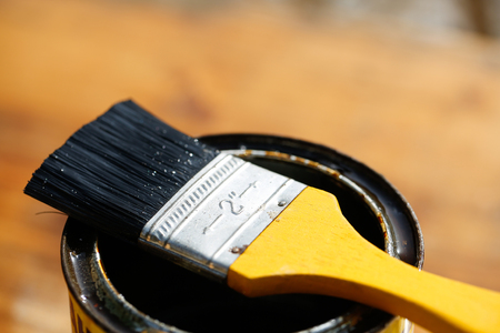 doityourself: Brush resting on a tin can of protective paint for wood treatment against weathering, insects and fungus. Outdoor protection, carpentry, hard at work, home improvement, do-it-yourself concept. Stock Photo