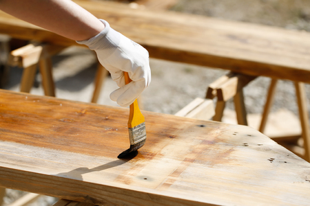 sawhorse: Painting wood with wood protection paint  for weathering, fungus and insects on sawhorses. Outdoor protection, carpentry, hard at work, home improvement, do-it-yourself concept.