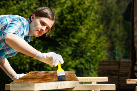 sawhorse: Woman applying and protecting garden furniture with fresh wood treatment paint. Outdoor protection, carpentry, hard at work, home improvement, do-it-yourself concept.