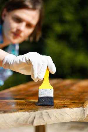 quality home: Woman carpenter inspecting her work after treating wood with protection paint. Outdoor protection, carpentry, hard at work, quality control, home improvement, do-it-yourself concept.