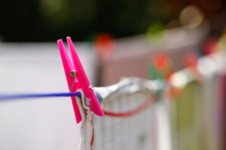 vida natural: Pinzas de la ropa que llevan a cabo lavadero en la línea de secado, el secado de la ropa al aire libre en el aire fresco, el viento y el sol. Las tareas del hogar, la vida familiar, el hogar, la vida natural y el concepto de estilo de vida.