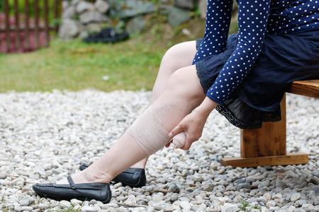 Vrouw met pijnlijke spataderen en spataderen op haar benen, het toepassen van drukverband, self-helpen zichzelf.