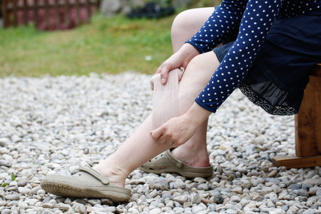 Woman with painful varicose and spider veins on her legs, applying compression bandage, self-helping herself.