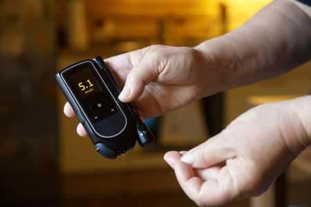 Diabetic patient testing her blood for sugar level at home; normal blood sugar level. Stock Photo