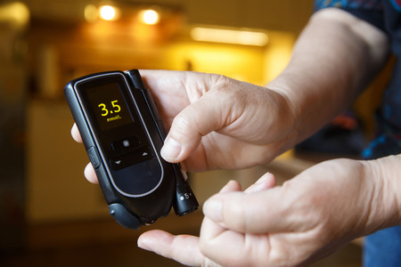 hypoglycemic: Hypoglycemic diabetic patient testing her blood for sugar level at home; low blood sugar. Medical process, self-diagnose, common metabolic, widespread and modern epidemic disease concept.