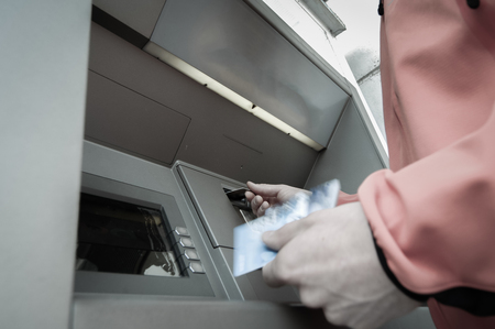 heist: Man standing in front of an ATM machine, withdrawing money, holding a stash of credit and debit cards. 247 banking, automated banking, money fraud, debt and financial crisis concept.