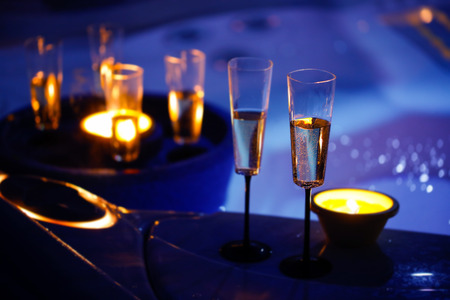 Extravagant, private romantic candlelit champagne glasses. Love, celebration, relax, romance, luxurious vacation, wellness spa concept. Stock Photo