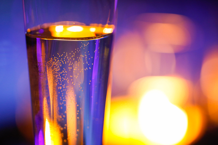 candlelit: Close-up of candlelit glass with sparkling champagne. Love, celebration, relax, romance, luxurious vacation, wellness spa concept. Stock Photo
