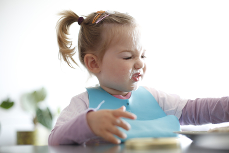 Little girl toddler picking her food, making faces. Childhood problems, picky eater, eating habits, terrible two concept. Stock Photo