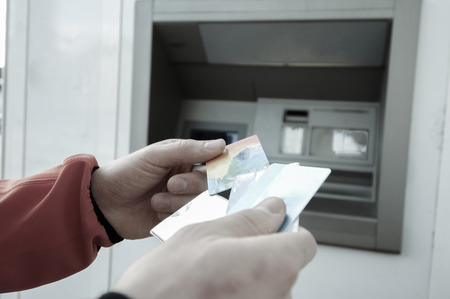 indebted: Man standing in front of an ATM machine, withdrawing money, holding a stash of credit and debit cards. 247 banking, automated banking, money fraud, debt and financial crisis concept.