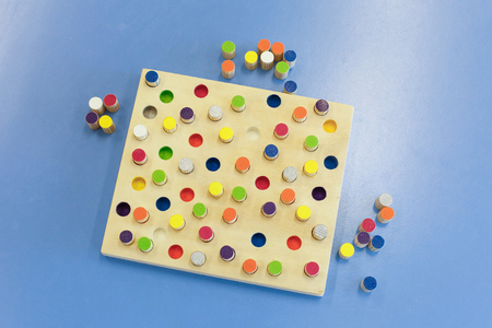 educational: Do-it-yourself educational wooden colorful game, made for stacking, arranging and building. Learning through experience concept, creative playing and educational approach concept. Stock Photo
