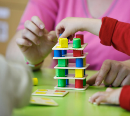 Children playing with homemade, do-it-yourself educational toys, stacking and arranging colorful pieces. Learning through experience concept, gross and fine motor skills, back to school concept. Stock Photo