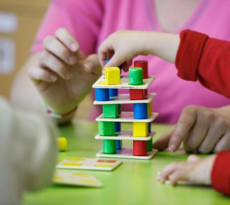 Enfants jouant avec maison, do-it-yourself jouets éducatifs, l'empilage et l'organisation des pièces colorées. Apprentissage par l'expérience concept, brute et de la motricité fine, de retour au concept de l'école.