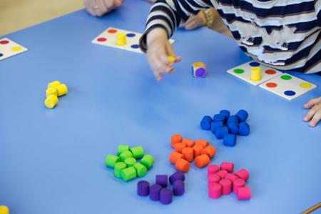 自家製、日曜大工の教育おもちゃで遊んで、配置、色を並べ替えの子供。経験概念, 知能開発, 教育アプローチの概念を学習します。