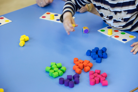 board game: Children playing with homemade, do-it-yourself educational toys, arranging and sorting colors. Learning through experience concept, intelligence development, educational approach concept.