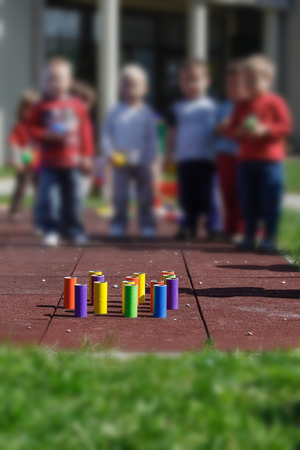 gross: Children playing with homemade, do-it-yourself educational toys, tube bowling. Learning through experience concept, gross and fine motor skills, educational approach concept.