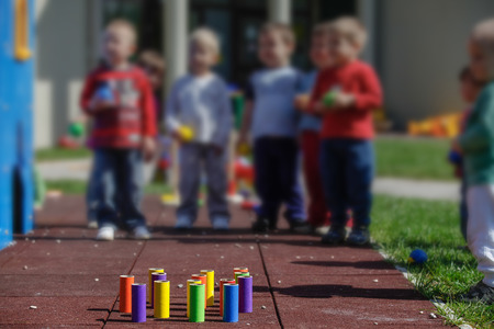 doityourself: Children playing with homemade, do-it-yourself educational toys, tube bowling. Learning through experience concept, gross and fine motor skills, educational approach concept.