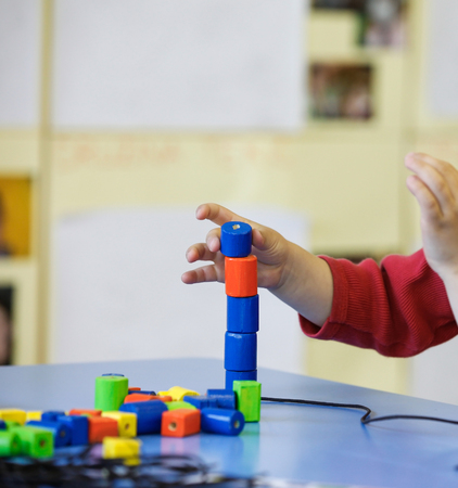 savvy: Child playing with homemade, do-it-yourself educational toys, stacking and arranging colorful pieces. Learning through experience concept, gross and fine motor skills, educational approach concept.