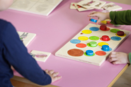 Children playing with homemade, do-it-yourself educational toys, arranging and sorting colors and sizes. Learning through experience concept, intelligence development, educational approach concept.