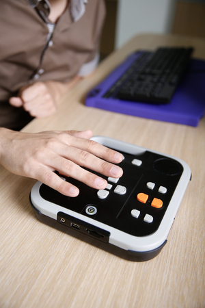 visual aid: Blind person using audio book player for visually impaired, listening to audio book on his computer. Blindness aid, visual impairment, independent life concept.