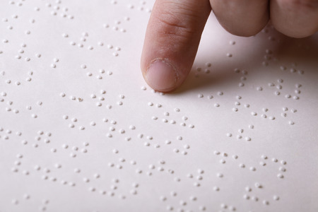 braille: Blind person touching book, written in braille writing, reading it. Blindness aid, visual impairment, independent life concept.