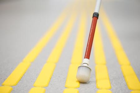 Blind voetgangers lopen en het detecteren van markeringen op tactiele bestrating met geweven grondoppervlak indicatoren voor blinden en slechtzienden. Blindheid hulp, visuele handicap, zelfstandig leven concept. Stockfoto