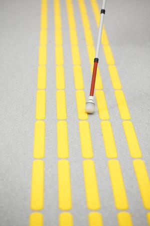 Blinder Fußgänger, und zum Erfassen Markierungen auf taktile Pflasterung mit texturierten Bodenindikatoren für Blinde und Sehbehinderte. Erblindung Hilfe, Sehstörungen, unabhängiges Leben-Konzept.