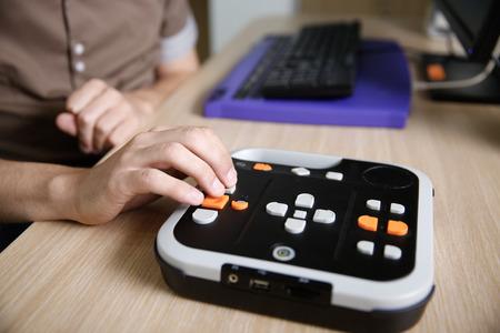 Blinde persoon met behulp van audio-boek speler voor blinden en slechtzienden, het luisteren naar audio-boek op zijn computer. Blindheid hulp, visuele handicap, zelfstandig leven concept.