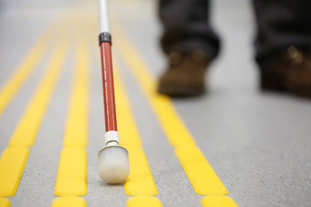 adjusted: Blind pedestrian walking and detecting markings on tactile paving with textured ground surface indicators for blind and visually impaired. Blindness aid, visual impairment, independent life concept. Stock Photo