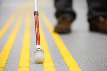 Blinder Fußgänger, und zum Erfassen Markierungen auf taktile Pflasterung mit texturierten Bodenindikatoren für Blinde und Sehbehinderte. Erblindung Hilfe, Sehstörungen, unabhängiges Leben-Konzept. Standard-Bild