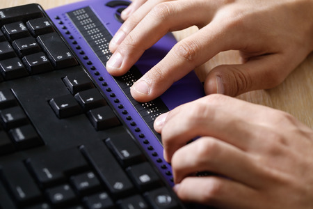 blind person: Blind person using computer with braille computer display and a computer keyboard. Blindness aid, visual impairment, independent life concept.