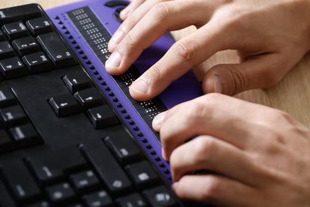 braille: persona ciega que usa el ordenador con la pantalla del ordenador braille y un teclado de ordenador. ayuda ceguera, discapacidad visual, el concepto de vida independiente.