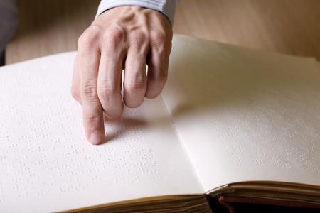 braille: Ciego tocando libro, escrito en la escritura en braille, leyéndolo. ayuda ceguera, discapacidad visual, el concepto de vida independiente. Foto de archivo