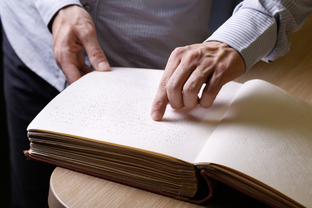 person writing: Blind person touching book, written in braille writing, reading it. Blindness aid, visual impairment, independent life concept.