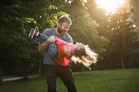 Devoted Vater seine Tochter in den Kreisen, Kleben, Spiel Spinnen, die Spaß an einem hellen, sonnigen Tag in der Natur haben. Elternschaft, Lifestyle, Erziehung, Kindheit und Familie Konzept.