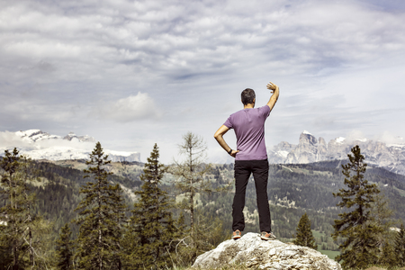right way: Hiker on a mountain top pasture looking for the right way in alpine landscape, being lost. Active lifestyle, natural environment, orientation and sports concept. Dramatic sky in the background. Stock Photo