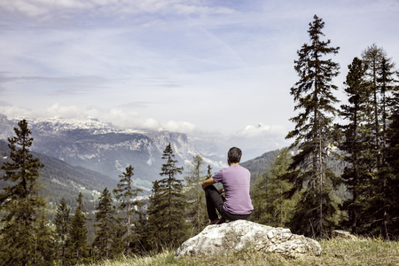 Hiker sitting on rock on a mountain top in beautiful alpine landscape. Active lifestyle, natural environment, meditation, serenity and sports concept. Dramatic sky in the background. Stock Photo