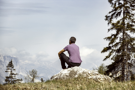 enjoy space: Hiker sitting on rock on a mountain top in beautiful alpine landscape. Active lifestyle, natural environment, meditation, serenity and sports concept. Dramatic sky in the background. Stock Photo