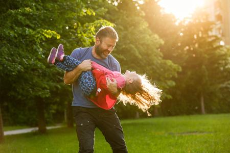 父円で娘を回転、結合、再生、明るい、晴れた日の自然で楽しい時を過すを捧げた。親、ライフ スタイル、子育て、子供と家族の生活概念。