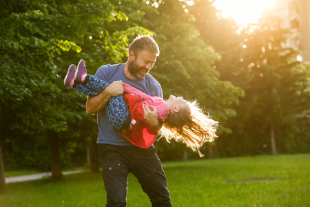 father daughter: Devoted father spinning his daughter in circles, bonding, playing, having fun in nature on a bright, sunny day. Parenthood, lifestyle, parenting, childhood and family life concept.