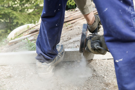 doityourself: Construction worker cutting a reinforced concrete pillar for installation with professional machine. Construction business, do-it-yourself, dirty and dangerous work around the house concept.