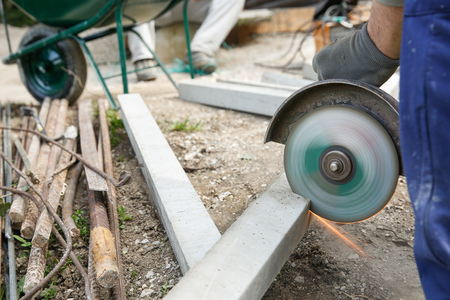 doityourself: Construction worker cutting a reinforced concrete pillar for installation with coworker in the background resting. Construction business, do-it-yourself, dirty and dangerous work around the house concept.