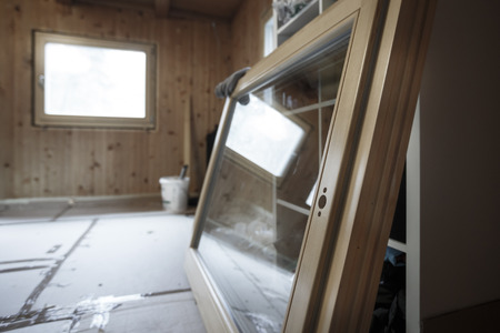 New efficient, three pane wooden window prepared for installation in an old wooden house, changing wasteful old windows. Home renovation, sustainable living, energy efficiency concept. Standard-Bild