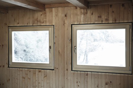 wasteful: New efficient, three pane wooden windows installed in an old wooden house, replacing wasteful old windows. Home renovation, sustainable living, energy efficiency concept.