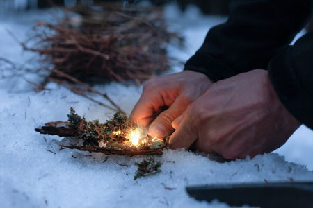 Man lighting a fire in a dark winter forest, preparing for an overnight sleep in nature, warming himself with DIY fire. Adventure, scouting, survival concept. Archivio Fotografico