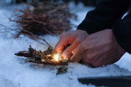 Man Beleuchtung ein Feuer in einem dunklen Winterwald, die Vorbereitung für eine Nacht Schlaf in der Natur, wärmte sich mit DIY Feuer. Abenteuer, Scouting, das Überleben Konzept.