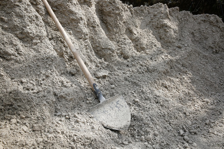 cement pile: Shovel lying on a pile of construction sand and gravel for concrete mixing. Construction business and material, do-it-yourself, manual work, having a break concept.