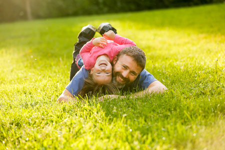 devoted: Devoted father and daughter lying on grass, enjoying each others company, bonding, playing, having fun in nature on a bright, sunny day. Parenthood, lifestyle, childhood and family life concept.