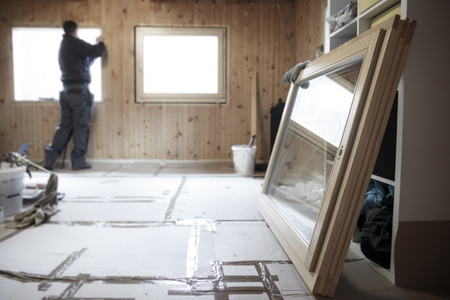 Worker in the background installing new, three pane wooden windows in an old wooden house, with a new window in the foreground. Home renovation, sustainable living, energy efficiency concept.